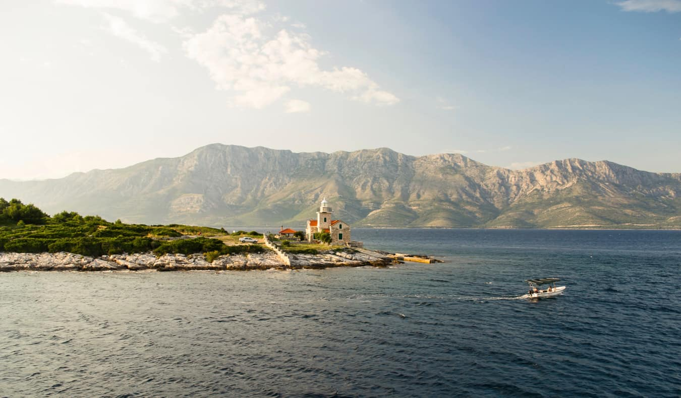 An isolated building on the coast of Hvar, Croatia with mountains in the background