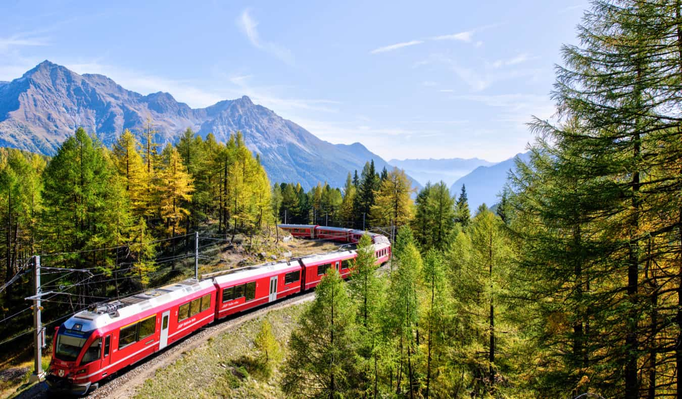 A high-speed train traveling through the snowy mountains of Europe