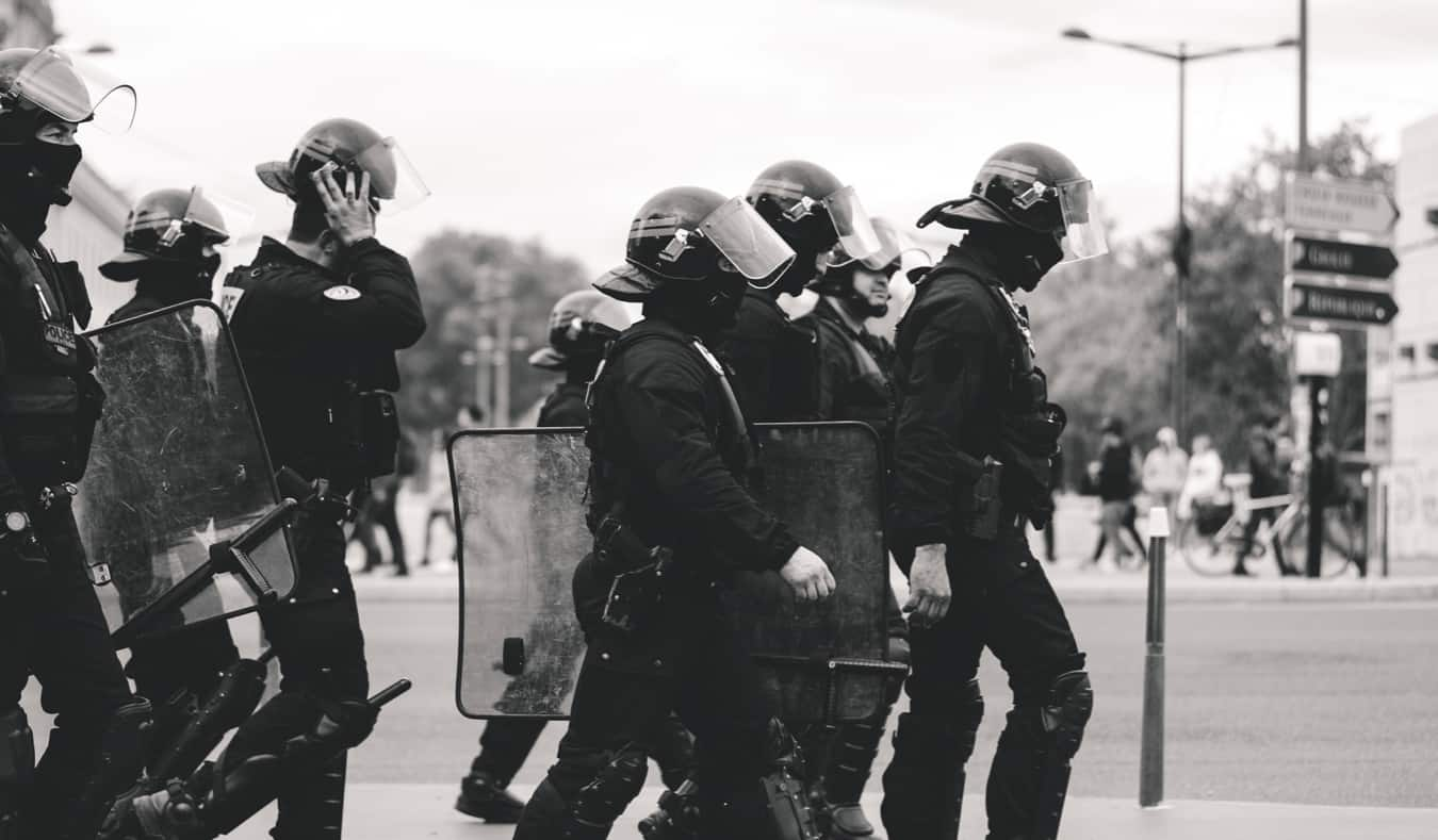 A black and white photo of riot police in Lyon, France