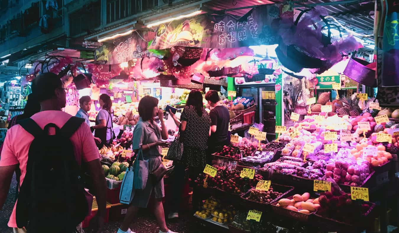 a small food market and the bustling streets of Hong Kong at night