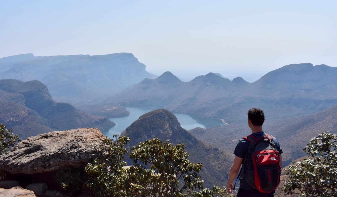 Nomadic Matt hiking in Africa looking out over the distant mountains