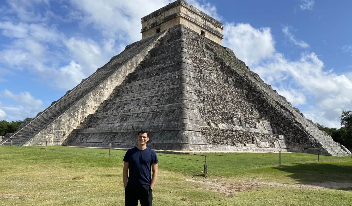 Nomadic Matt posing for a photo near Chichen Itza in Mexico