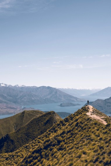 A person posing at the top of Roy's Peak in Wanaka, NZ