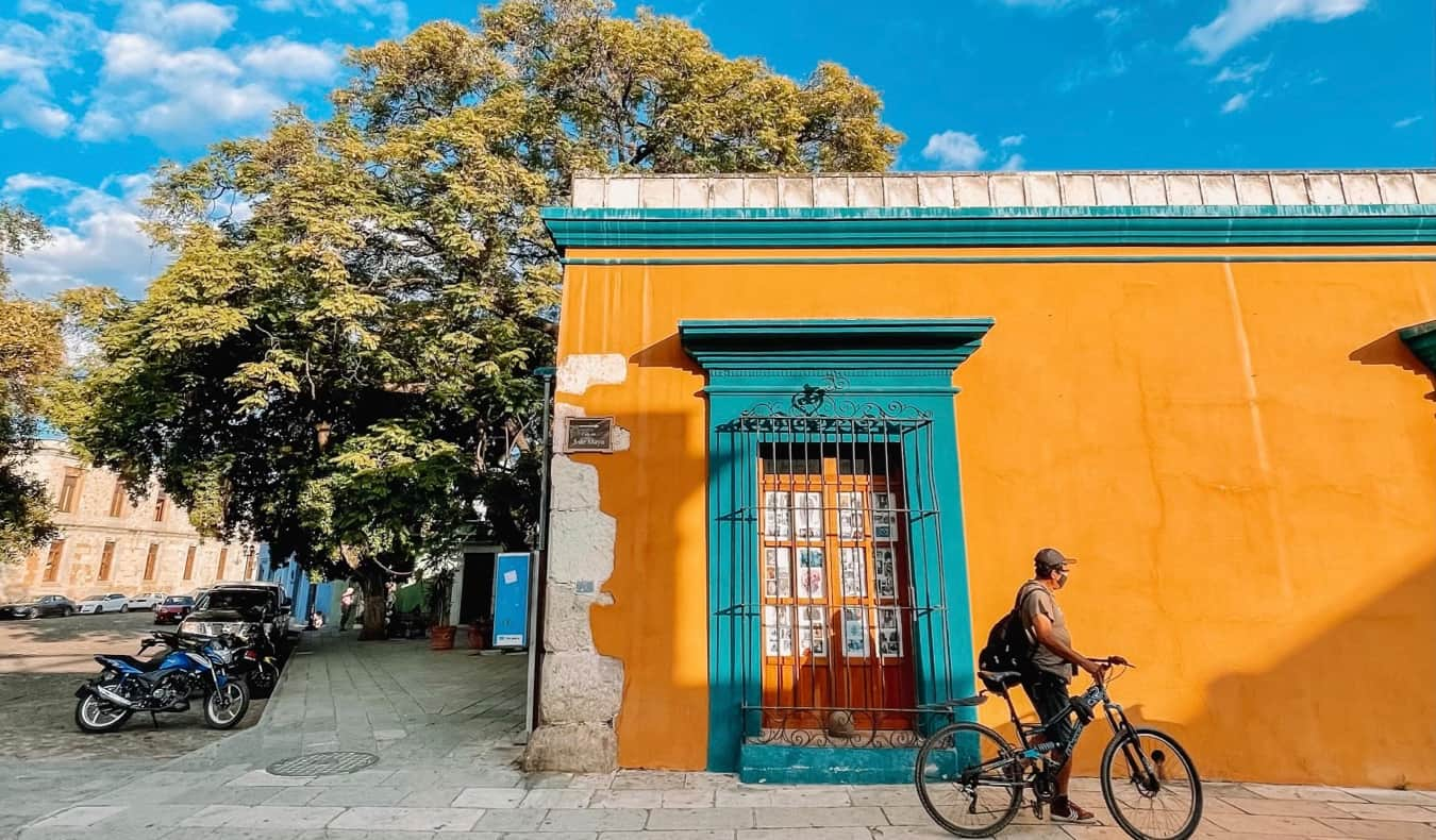 A local man in Oaxaca, Mexico with a bicycle near a colorful building