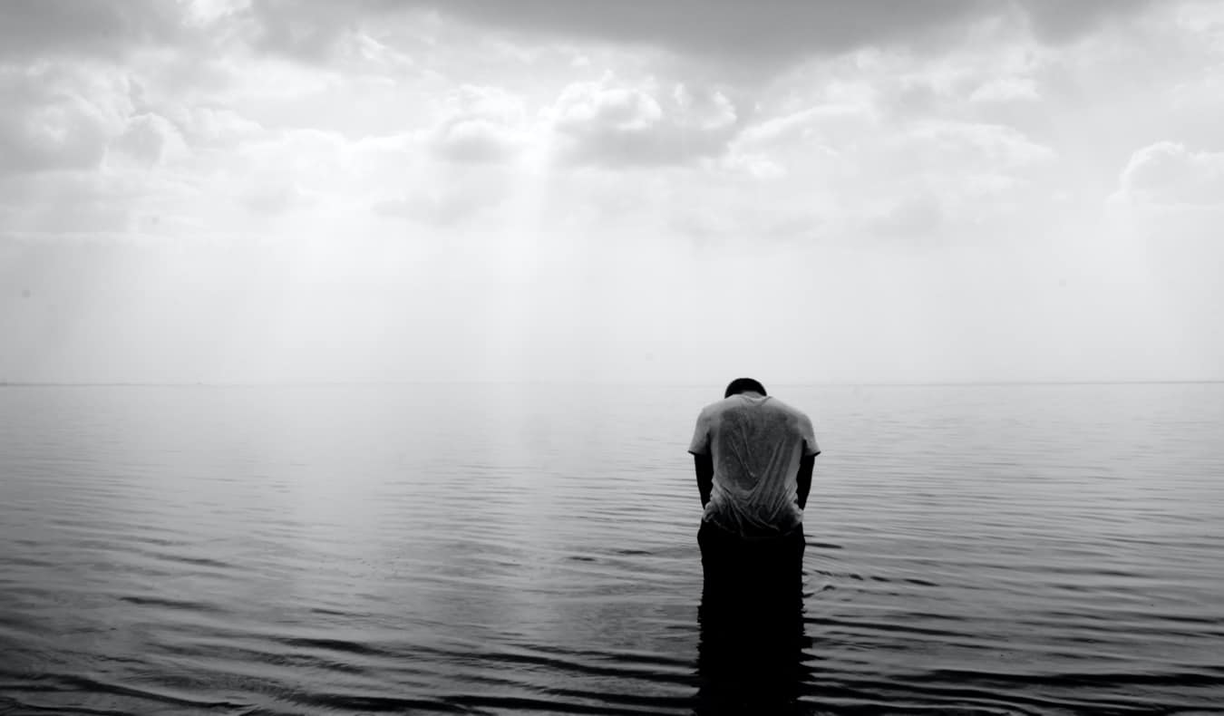 A black and white photo of a lone traveler alone in the water