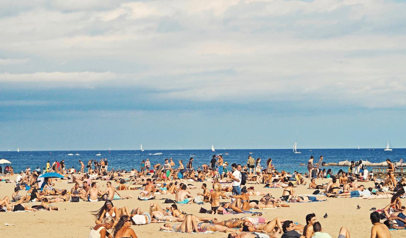 People chilling on the beach in Barcelona, Spain