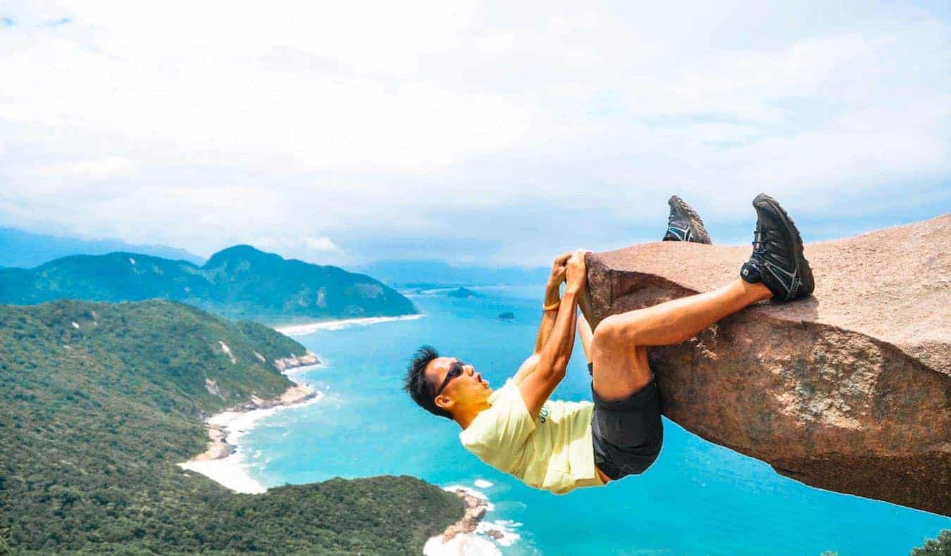 Rax, a solo digital nomad, hanging off a rock abroad