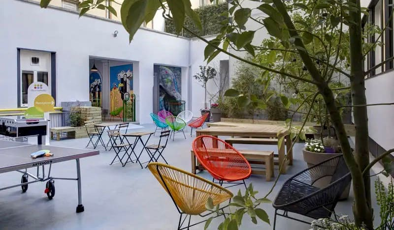 The outdoor courtyard and common area at RomeHello hostel