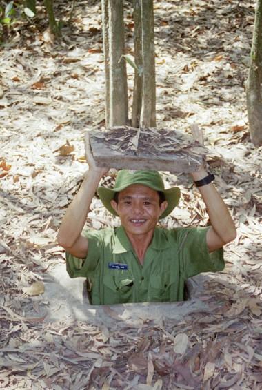 A Vietnamese man poking through the tiny CU Chi Tunnels in HCMC, Vietnam