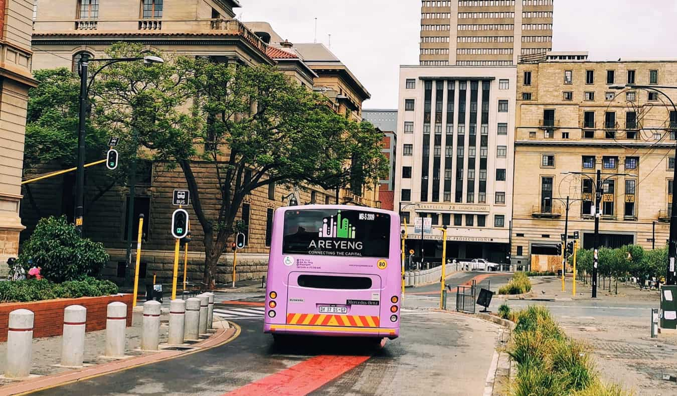 A coach bus driving in a city in South Africa