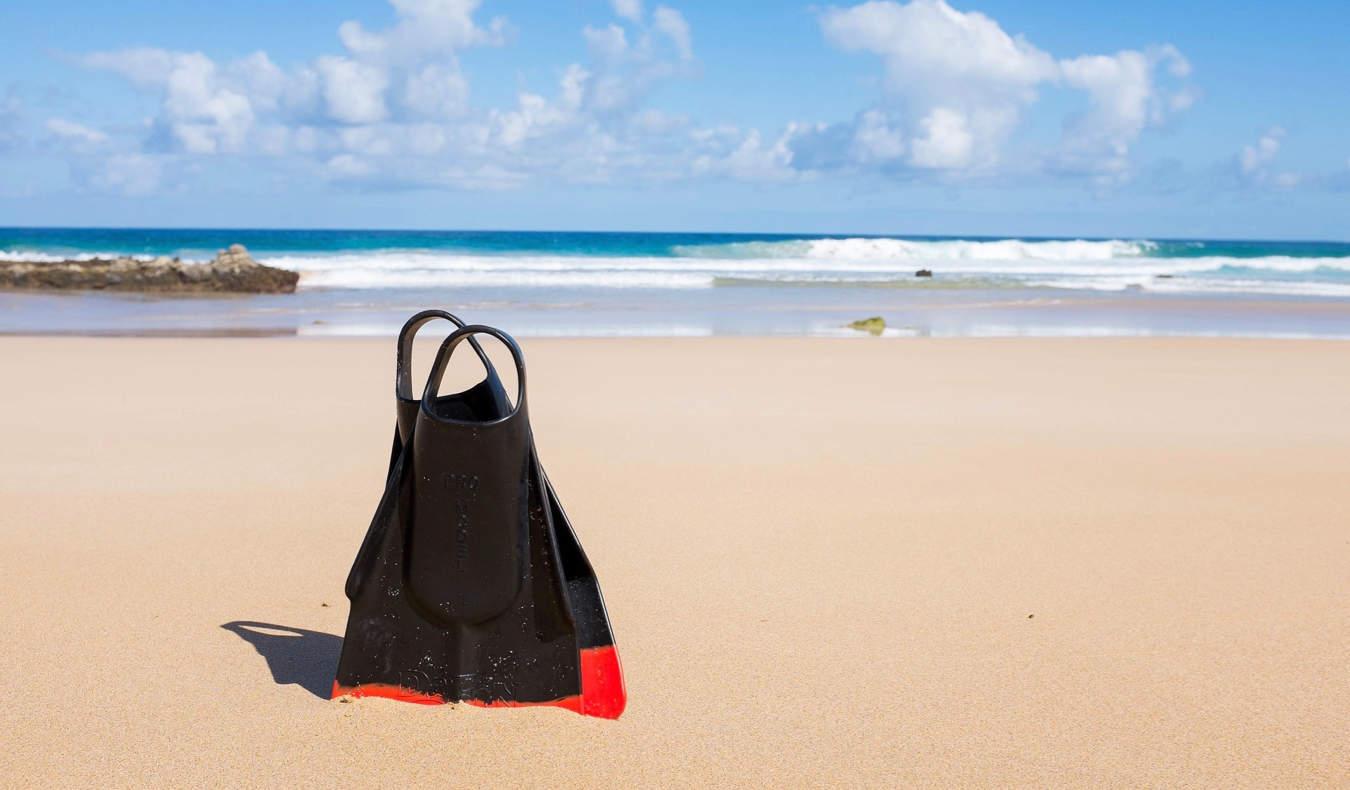 Scuba fins in the sand on a beautiful beach
