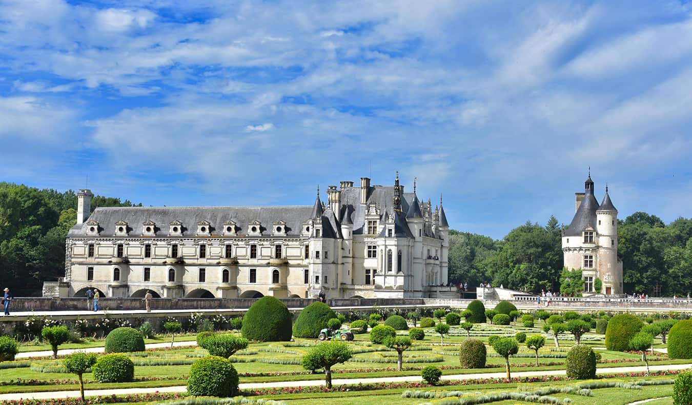 A chateaux in France and the surrounding gardens on a beautiful summer day