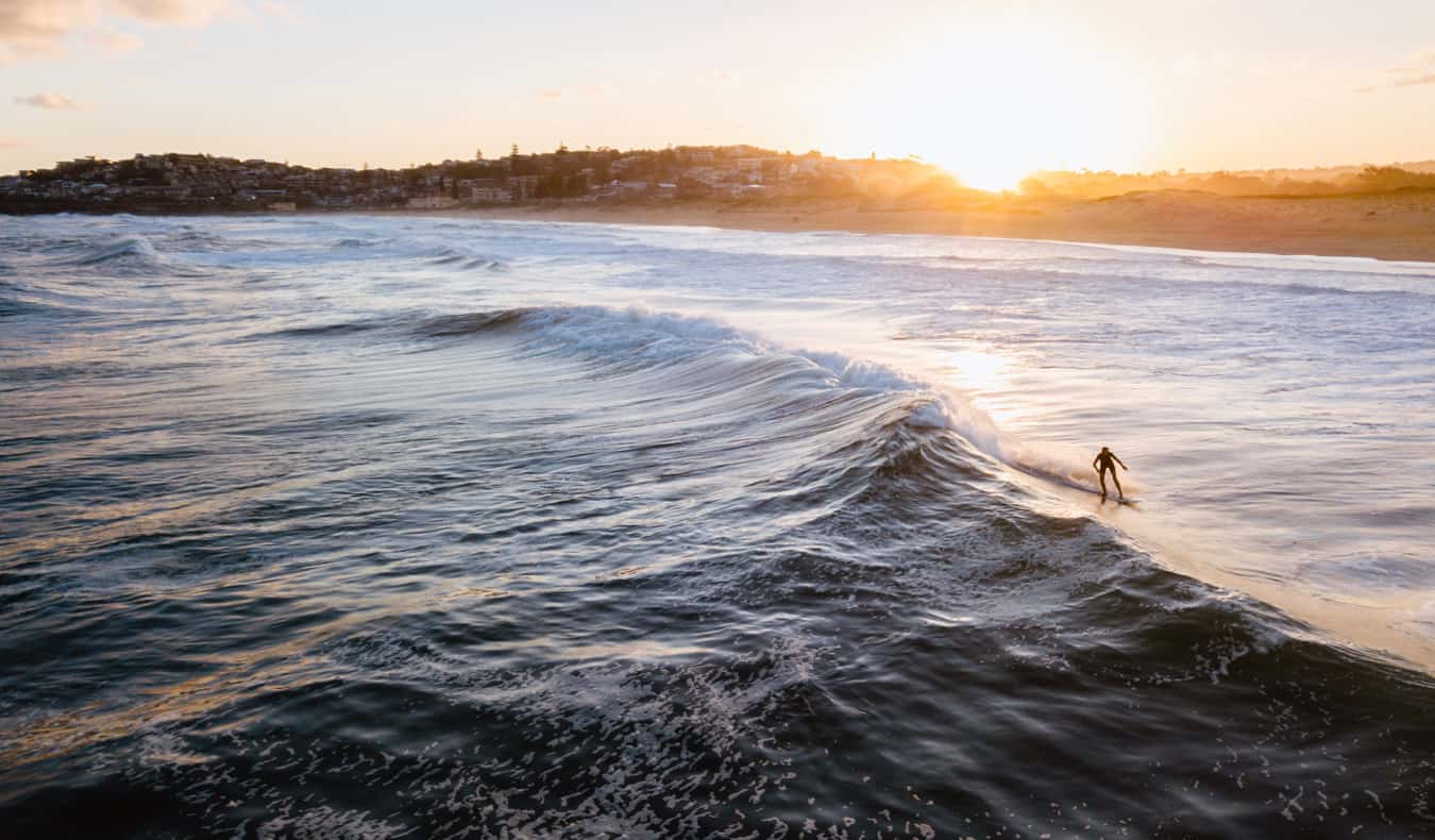 A surfer in the water surfing in Sydney, Australia