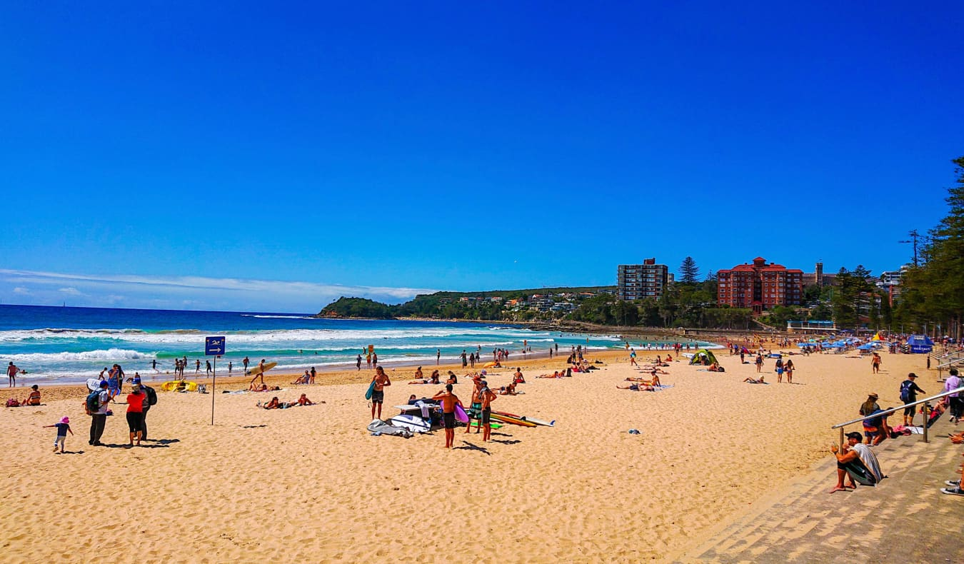 People enjoying Manly beach on a sunny day in Australia