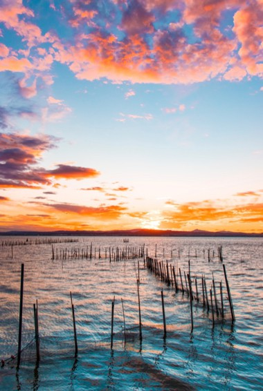 Sunset over the calm waters of Albufera in Valencia, Spain
