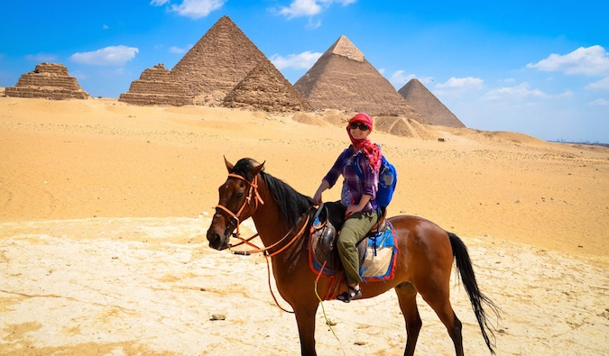Woman nomad riding a camel at the Pyramids in Egypt