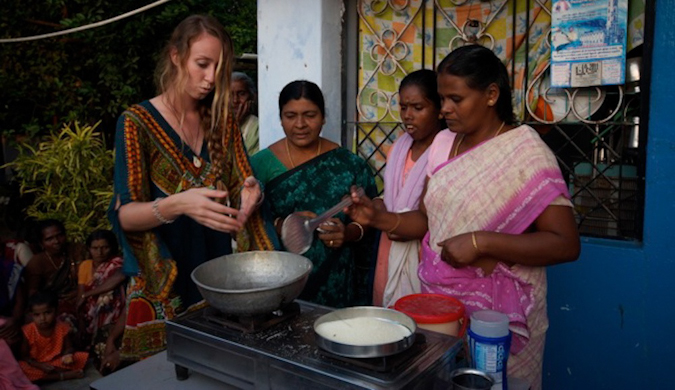 A solo female traveler making Indian food with locals