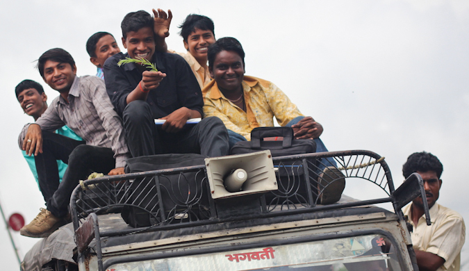 A group on locals on the top of a car as it moves