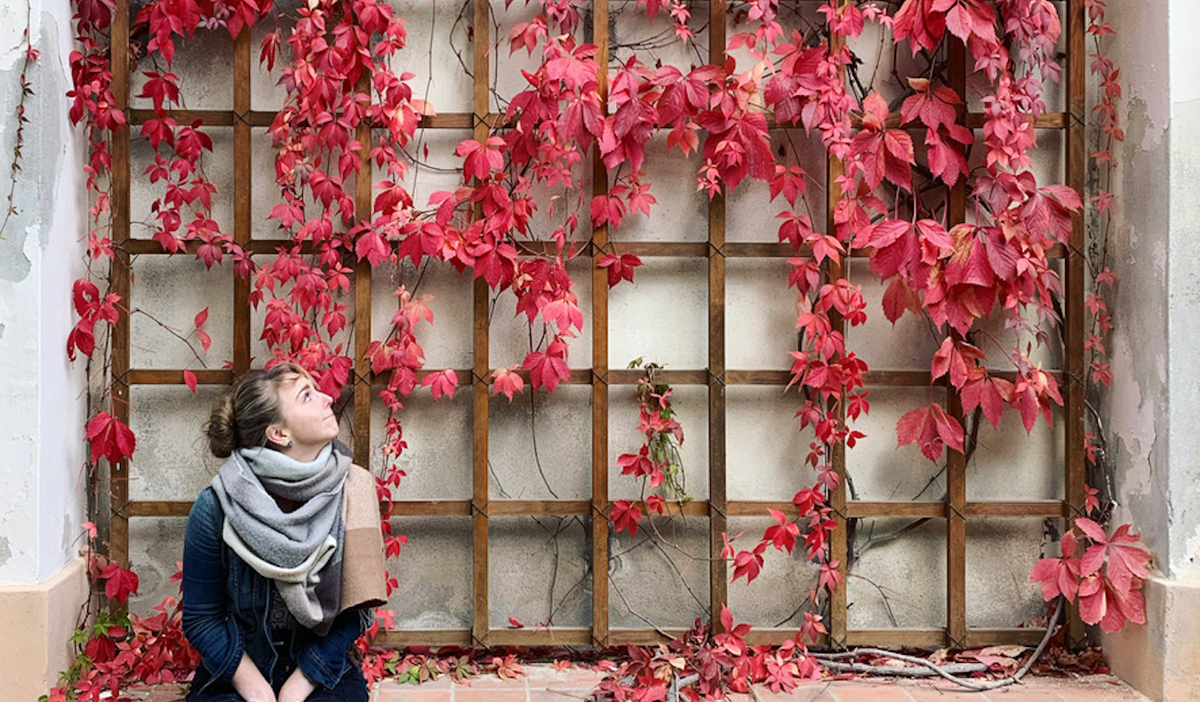 travel community member adrien with red leaves during the fall trip overseas