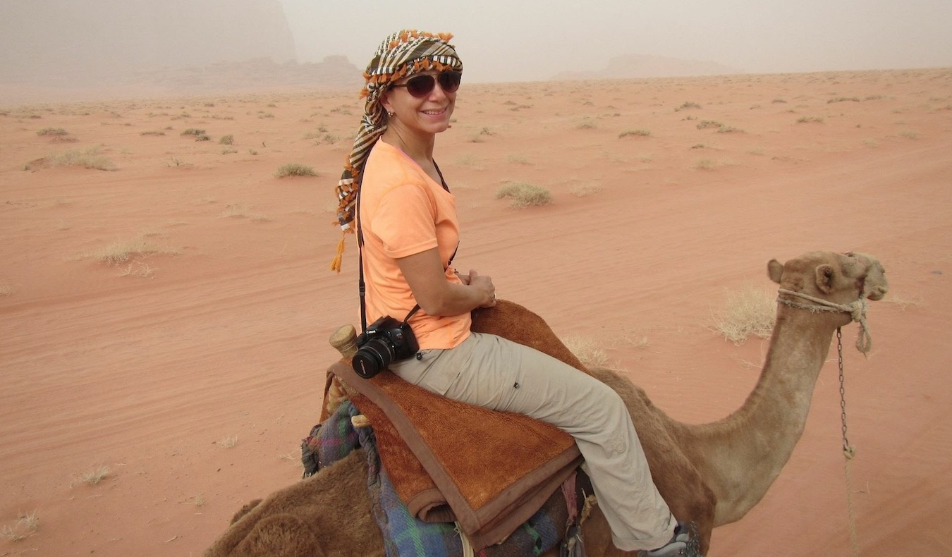 woman riding a camel in the desert