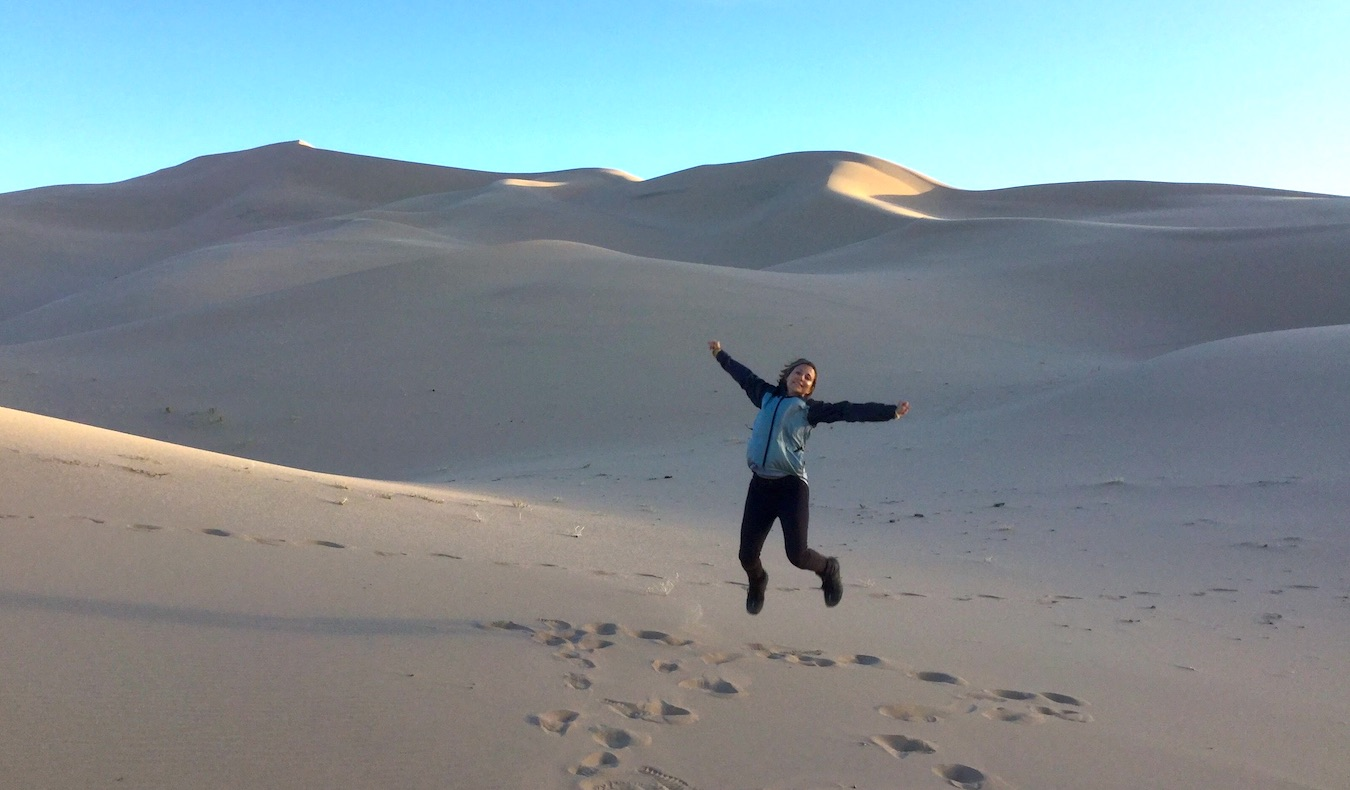 woman jumping in the sand dunes in the desert