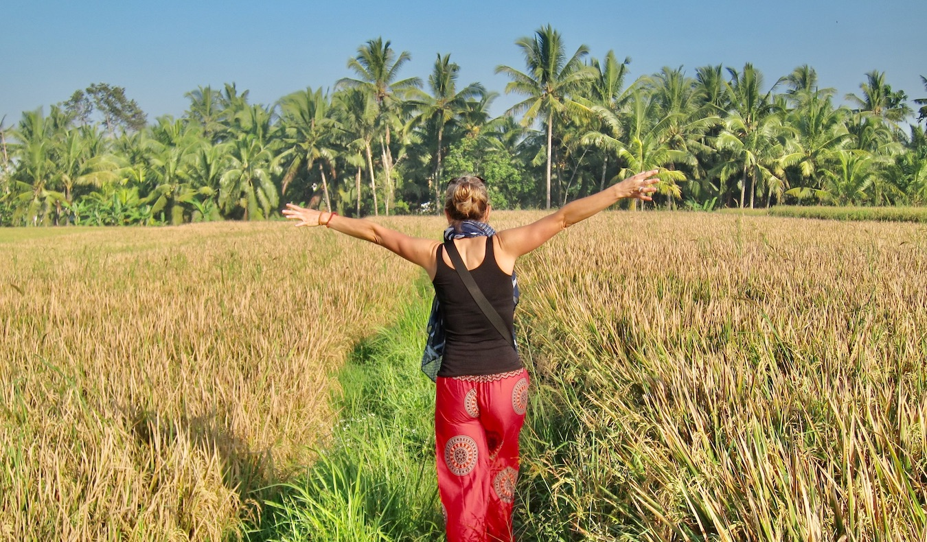 woman walking through a field with palm trees
