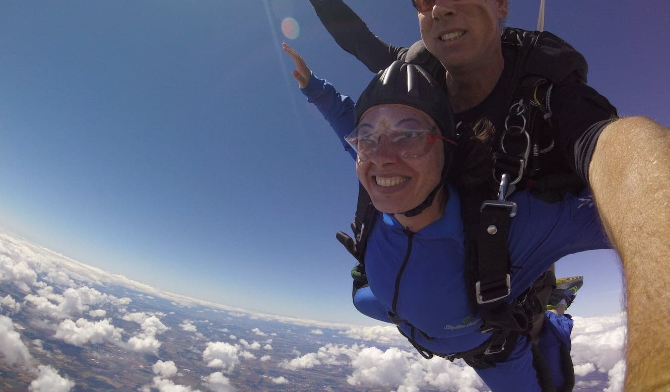 traveler skydiving and smiling