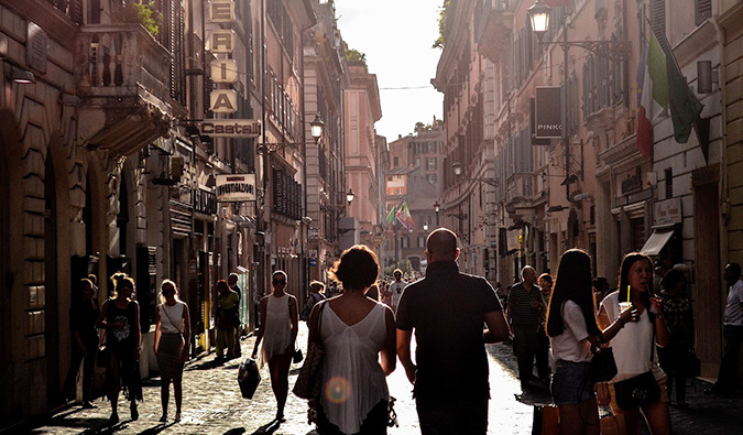 A couple walking down a busy street in Europe surrounded by tourists and locals
