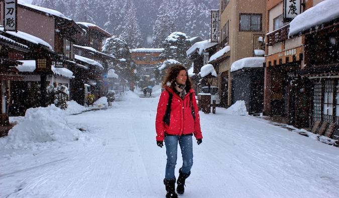 A solo female traveler walking on a snowy road in Japan in winter