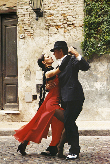 a woman in red and a man dressed in black perform the tango in Argentina