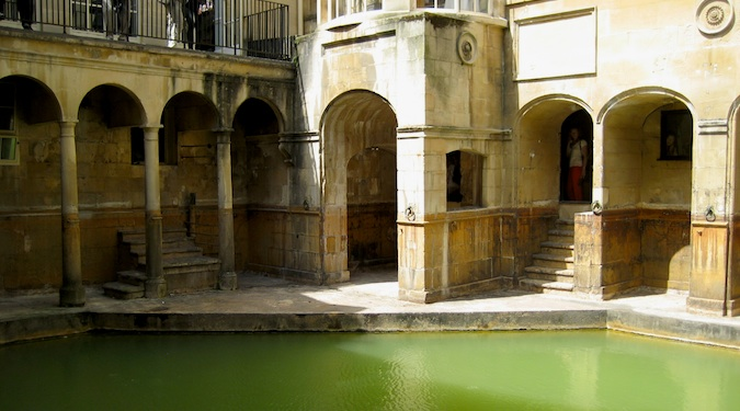The arches doorways of the Roman Baths with green water