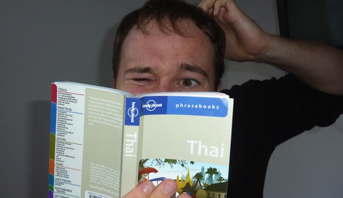 Man looking confused holding a Thai Lonely Planet phrasebook