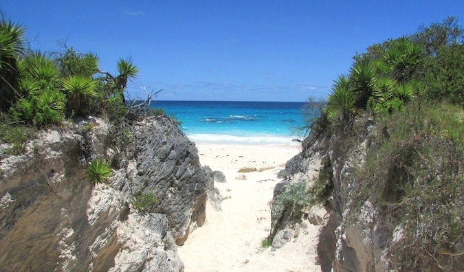 Sandy entrance to the Caribbean beach flanked by two large grassy rocks