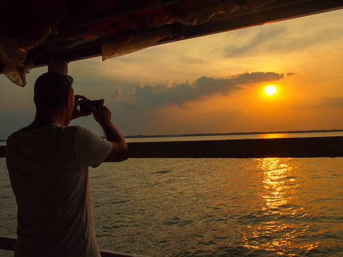 Dave Dean taking a photo of the sunset abroad with his smartphone