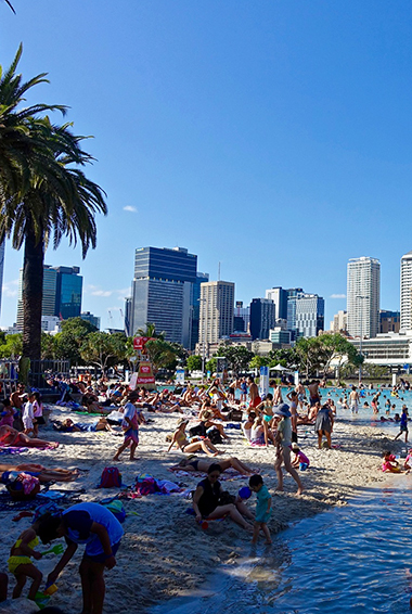 a beach and palm trees in front of the city skyline at South Bank Parklands, Brisbane