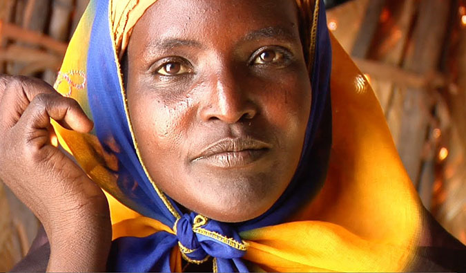 A woman from Africa looking at the camera during the filming of One Day in Africa