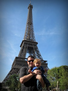 Cameron holding his baby son up by the Eiffel Tower