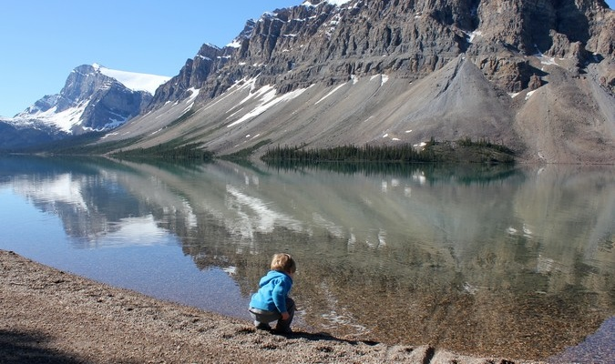 Little boy bends down to touch the beautiful lake overseas