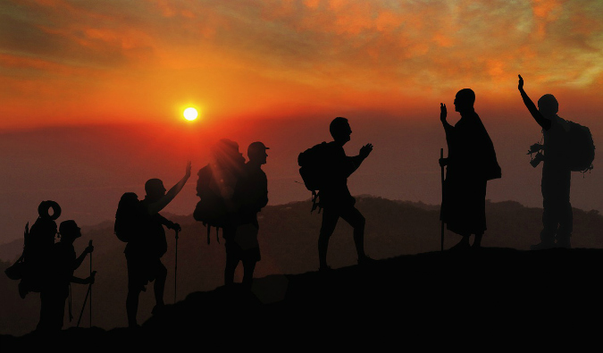 A group of travelers climbing a mountain during a bright sunset