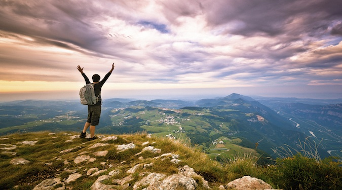 Nomadic backpacking hiker standing at the top of a mountain excited