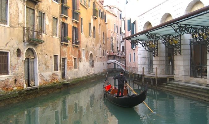 Gorgeous gondola with tourists in the canals of venice, Italy