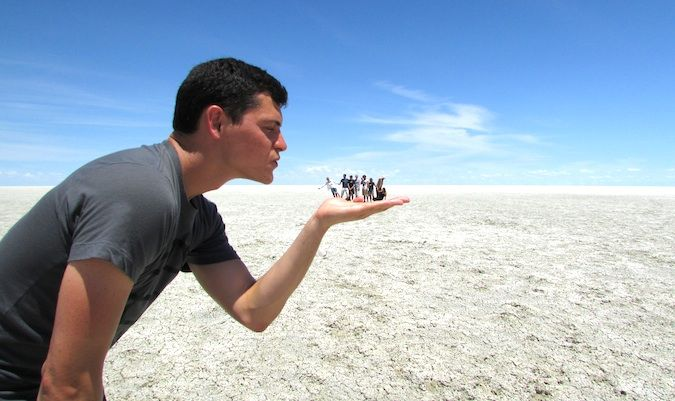 Nomadic Matt and travel friends posing like a tourist on a salt flat