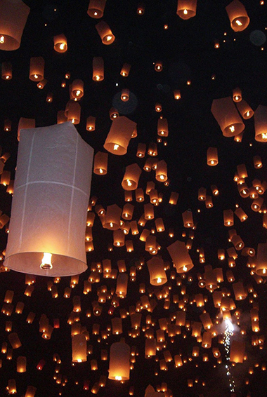 glowing lanterns released into the sky at the Yi Peng Festival in Chiang Mai
