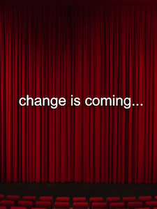 Red stage curtain with words saying change is coming...