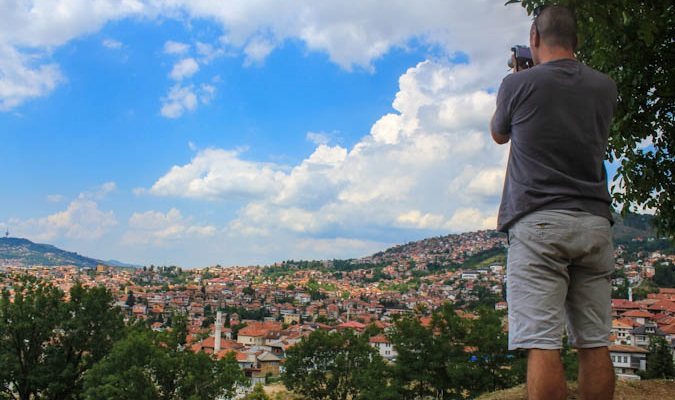 Dave takes a photo from the top of a mountain overseas while traveling