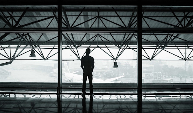 A black and white photo of a solo traveler standing alone in an airport