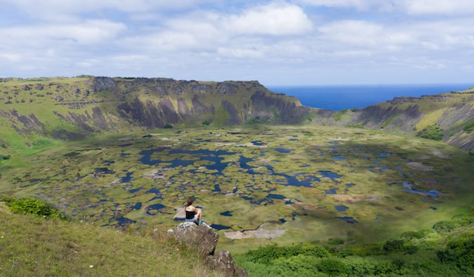 traveler sitting and looking at the pristine landscape on Easter Island