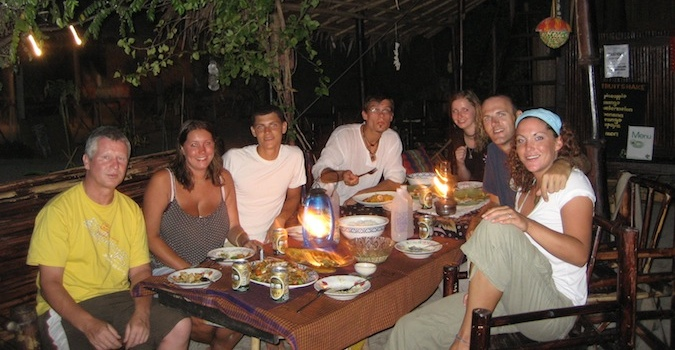 Eating dinner around a candlelit table with travelers outside in Thailand