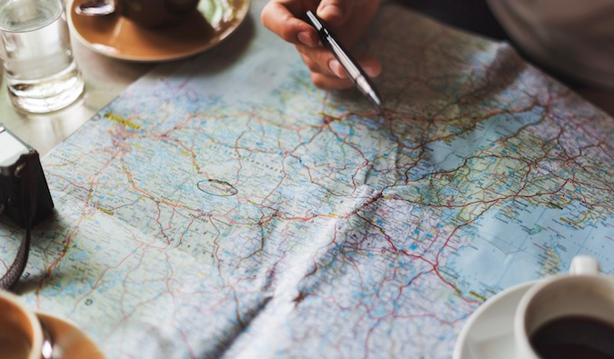 A person planning a Backpacking Trip to Europe with a map