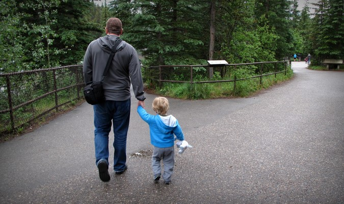 Dad and toddler walking through a park on vacation